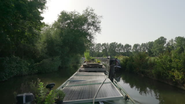 a narrow boat travels along the river stort on the essex and hertfordshire borders - ハートフォードシャー点の映像素材/bロール