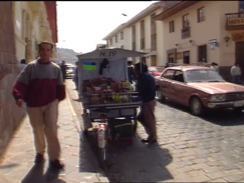 narrow brick sidewalk lined one way street w/ ambulantes w/ cart parked curbside people walking through fg - peruvian ethnicity stock videos and b-roll footage