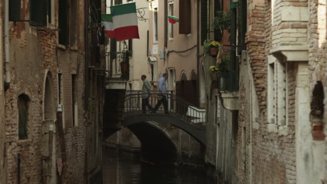 WS Narrow canal between buildings,with people crossing arch bridges in background / Venice,Veneto