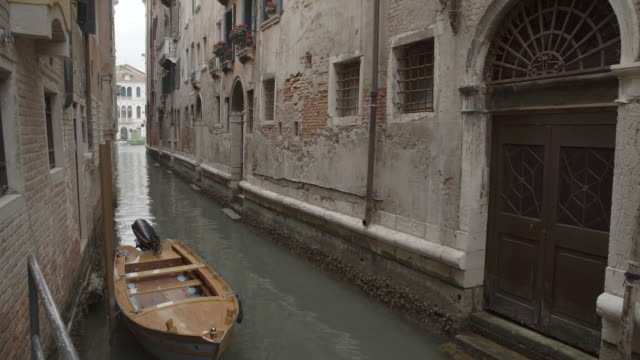 Narrow Canal with a boat / Venice, Italy