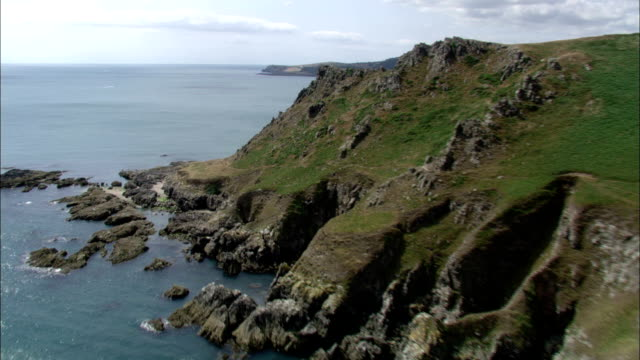 Narrow coastal roads circumvent rugged cliffs on the southwest coast of England. Available in HD.