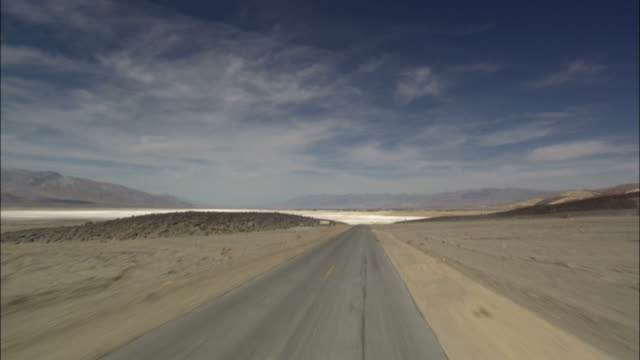 a narrow, desolate road leads to death valley. - terra brulla video stock e b–roll