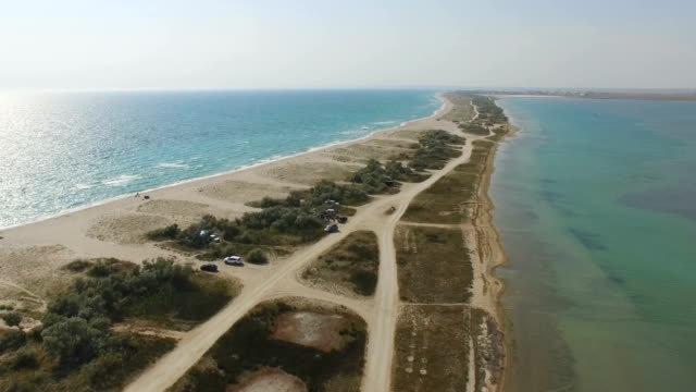 AERIAL: Narrow part of sandy land in blue sea