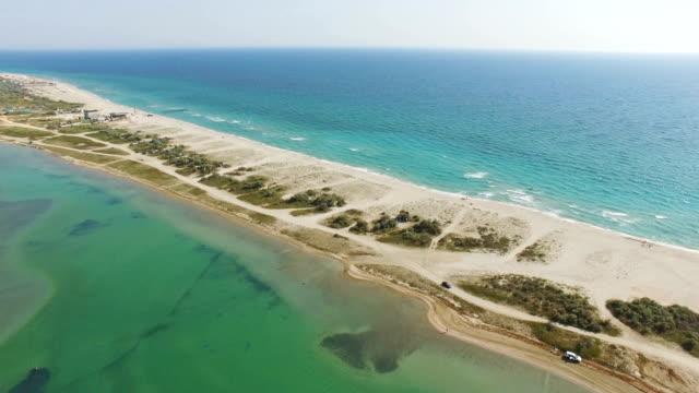 AERIAL: Narrow part of sandy land in shallow sea waters