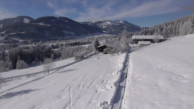 vidéos et rushes de a narrow, plowed track leads to a snow-covered mountain chalet. - bo tornvig