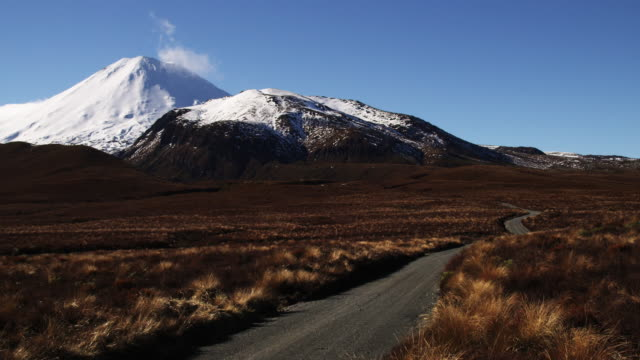 a narrow road stretches across a mountain landscape in new zealand. - tongariro national park stock videos & royalty-free footage