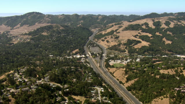 A narrow road winds through wooded hills in California.