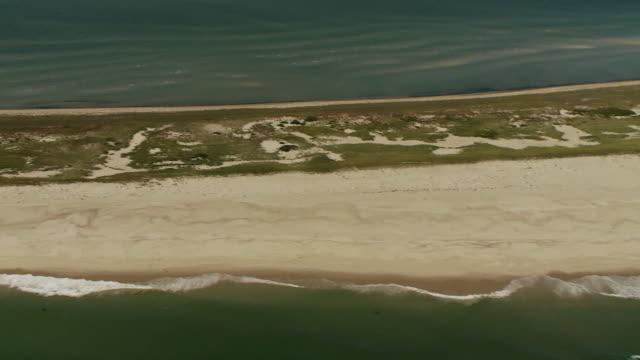 vídeos de stock e filmes b-roll de a narrow, sandy beach stretches out into the atlantic ocean. - banco de areia