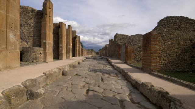 narrow stone street leads through the ruins of pompeii, italy - old ruin stock videos & royalty-free footage