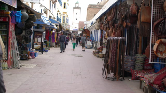 a narrow street in the medina (old town) of essaouira full of souvenir shops, morocco - narrow stock videos and b-roll footage