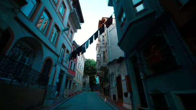 narrow streets of old istanbul, colorful clothes hanging on clothesline between buildings' windows - hanging stock videos & royalty-free footage