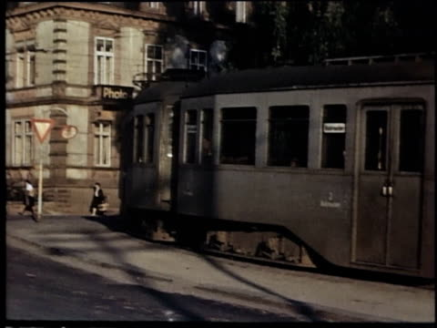 narrow-gauge mountain streetcars moving down street / garmisch, germany - baviera video stock e b–roll
