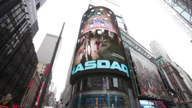 nasdaq exteriors looking straight on / tilt up / people crossing at intersection / various adds on screen nasdaq - centered on february 27, 2012 in... - ナスダック点の映像素材/bロール