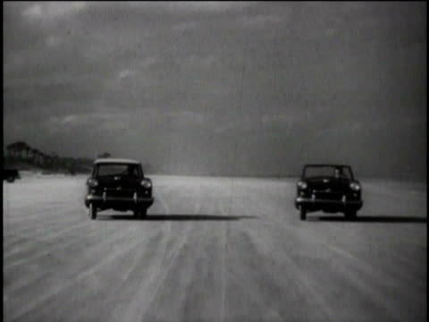 B/W WS Nash Metropolitan car driving toward camera on beach as another pulls up alongside it/ United States