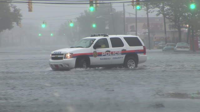 a nassau county police suv is forced to turn around as fast moving flood waters race across austin blvd in island park ny during hurricane irene's... - nassau stock videos & royalty-free footage