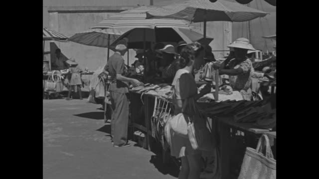 vidéos et rushes de nassau marketplace with women shopping for hats handbags and baskets / docked boats / workers timing sails on docked boats / note exact day not known - bahamas