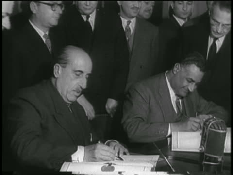 nasser alkuwatli at table signing united arab republic agreement / cairo / newsreel - 1958 stock videos & royalty-free footage
