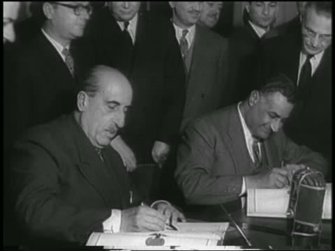 vídeos de stock e filmes b-roll de nasser alkuwatli at table signing united arab republic agreement / cairo / newsreel - 1958