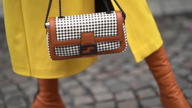 natalia verza aka mascarada wears a bold yellow long trench coat from fendi, a fendi black and white checked fendi bag with brown leather parts, on... - elegance stock videos & royalty-free footage