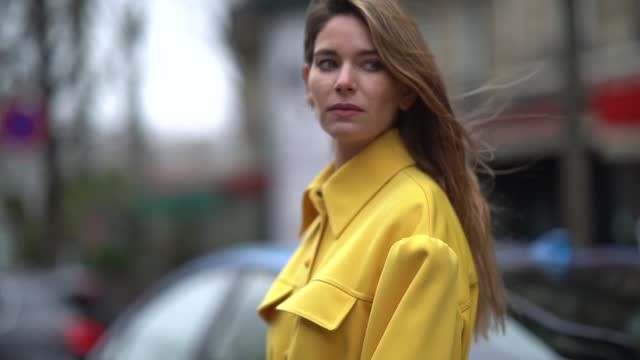 natalia verza aka mascarada wears earrings, a bold yellow long trench coat from fendi, a fendi black and white checked fendi bag with brown leather... - grace stock videos & royalty-free footage