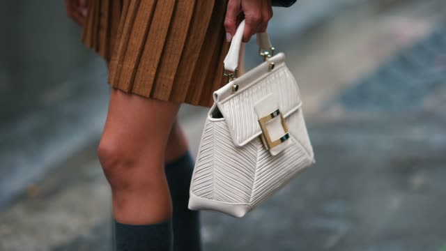 natalia verza wears a brown/orange pleated skirt, a black leather jacket, gray high socks, a white roger vivier bag, outside paul & joe, during paris... - skirt stock videos & royalty-free footage