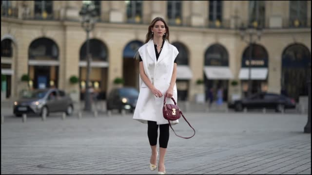 natalia verza wears a total look from miu miu, consisting in a white sleeveless long jacket, a black cropped top, a burgundy leather quilted bag,... - street style点の映像素材/bロール