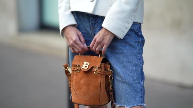 natalia verza wears a white jacket from balmain, a balmain belt, blue denim ripped shorts, a brown suede balmain bag, black shoes from prada, on... - shorts stock videos & royalty-free footage