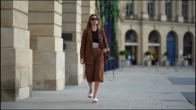 natalia verza wears celine sunglasses, a necklace, a black paco rabanne cropped top, a gestuz brown suede jacket, brown suede long shorts, white... - street style点の映像素材/bロール