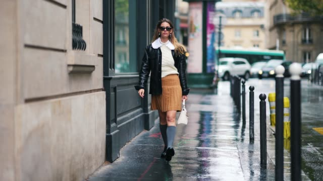 natalia verza wears sunglasses, a white wool woven pullover, a white ruffled collar, a brown/orange pleated skirt, a black leather jacket, gray high... - scarpe video stock e b–roll