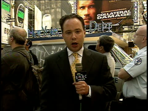 "nathan king reports for sabc from times square hours after the attack. ""collateral damage"" billboard, nypd sign in bg, & crowd looking upward behind... - terrorism stock videos & royalty-free footage"