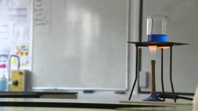 national audit office warns of effects of teacher shortages beaker of liquid sitting on stand above bunsen burner - bunsen burner stock videos & royalty-free footage