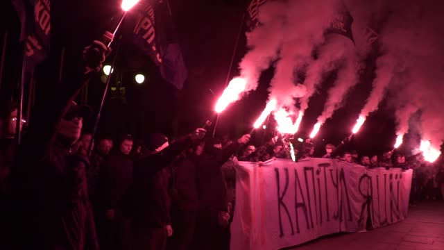 vídeos de stock e filmes b-roll de national corps's activists burn flares and hold a banner reading 'no to capitulation!' as they protest outside the presidential office in kiev,... - ucrânia bandeira