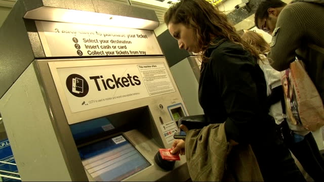 national express rail company allowed to keep london to essex franchise; rail passenger at ticket machine ticket being collected from tray - franchising stock videos & royalty-free footage