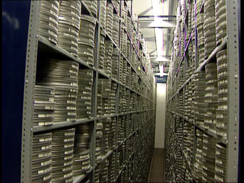 national film and television archive itn cbs man along between racks of film cans on motorised trolley ms member of staff on trolley twds between... - archives stock videos & royalty-free footage