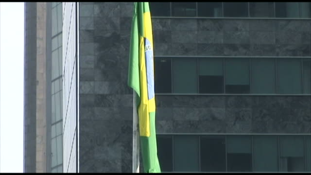 TD National flag in front of tall building and pedestrians walking on the sidewalk / Rio de Janeiro Brazil