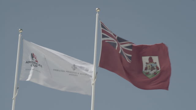 National flag of Bermuda Island and flag of America´s Cup fluttering in the wind at port of Hamilton