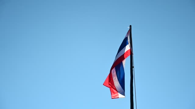 vidéos et rushes de national flag thailand is blowing with the wind on a clear day. - banderole signalisation