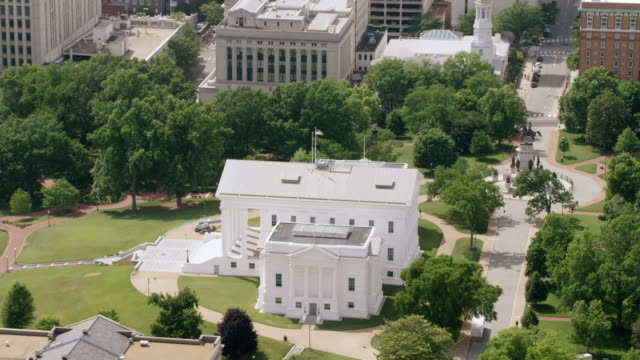 WS ZI AERIAL POV National flag waving on top of Virginia State Capitol building with city / Richmond, Virginia, United States