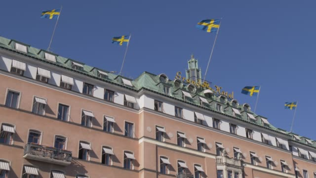 national flags flying on the grand hotel on swedens national day in june, stockholm, sweden, scandinavia, europe - swedish flag stock videos and b-roll footage
