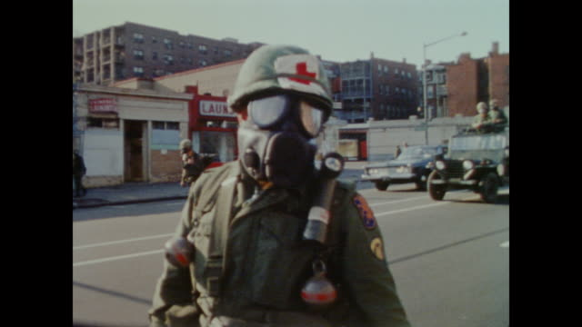 national guard medic walks along the city streets along with armed soldiers both walking and driving as part of a patrol in the wake of the 1968 riots - アメリカ黒人の歴史点の映像素材/bロール