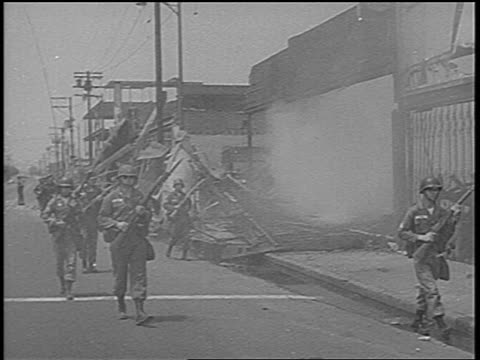 National Guard on city street past destroyed buildings / Watts race riots low angle / newsreel