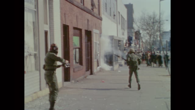 national guard soldiers carrying rifles let off smoke bombs to disperse crowds before running to help an injured man - assassination stock videos & royalty-free footage