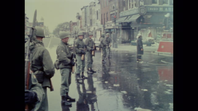 vídeos de stock e filmes b-roll de national guard soldiers provide armed patrol for firefighters as they douse the flames of the 1968 washington riots - 1968