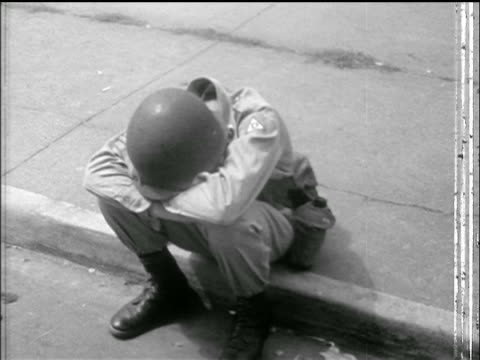 vídeos y material grabado en eventos de stock de national guard troop with helmet sits on curb with head on arms / little rock arkansas - 1957