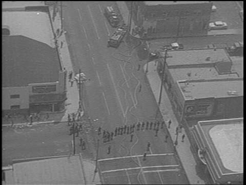 stockvideo's en b-roll-footage met national guard troops on city street after watts race riots low angle / newsreel - 1965