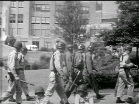 national guard troops walk in front of central high school / little rock, arkansas - 1957 stock-videos und b-roll-filmmaterial