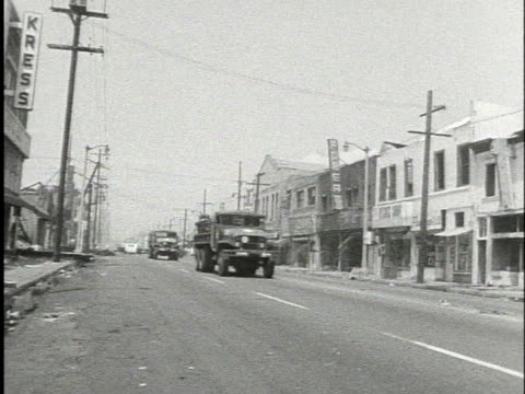 vídeos y material grabado en eventos de stock de national guard trucks drive on a street in watts after the riots there. - 1965