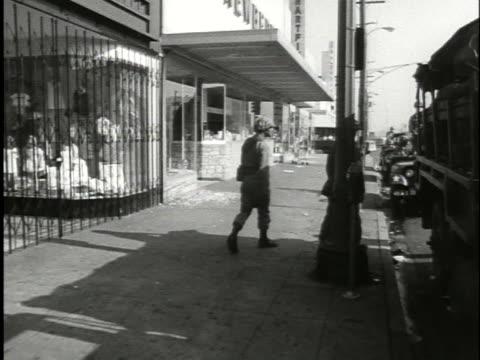 vídeos y material grabado en eventos de stock de national guardsmen stand guard in the aftermath of the watts riots in 1965. - 1965