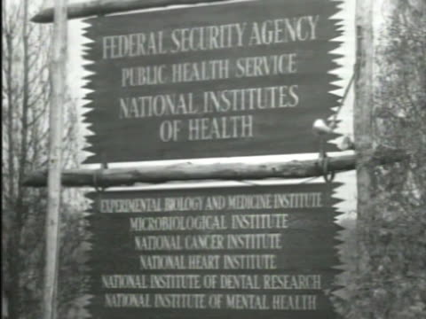 national institutes of health sign w/ inclusive departments below ws national institutes of health building w/ columned porch - bethesda maryland stock videos & royalty-free footage