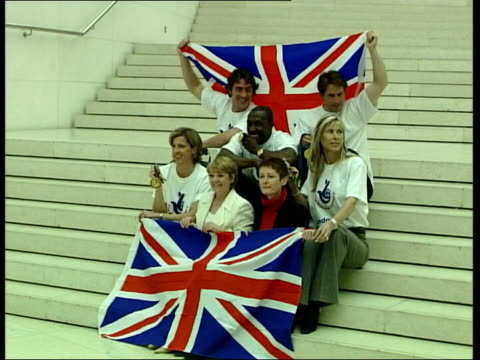 committee criticises government spending plans lib athletes posing with union jack flags as launching bid for olympic games 2012 - 2012年ロンドン夏季オリンピック点の映像素材/bロール